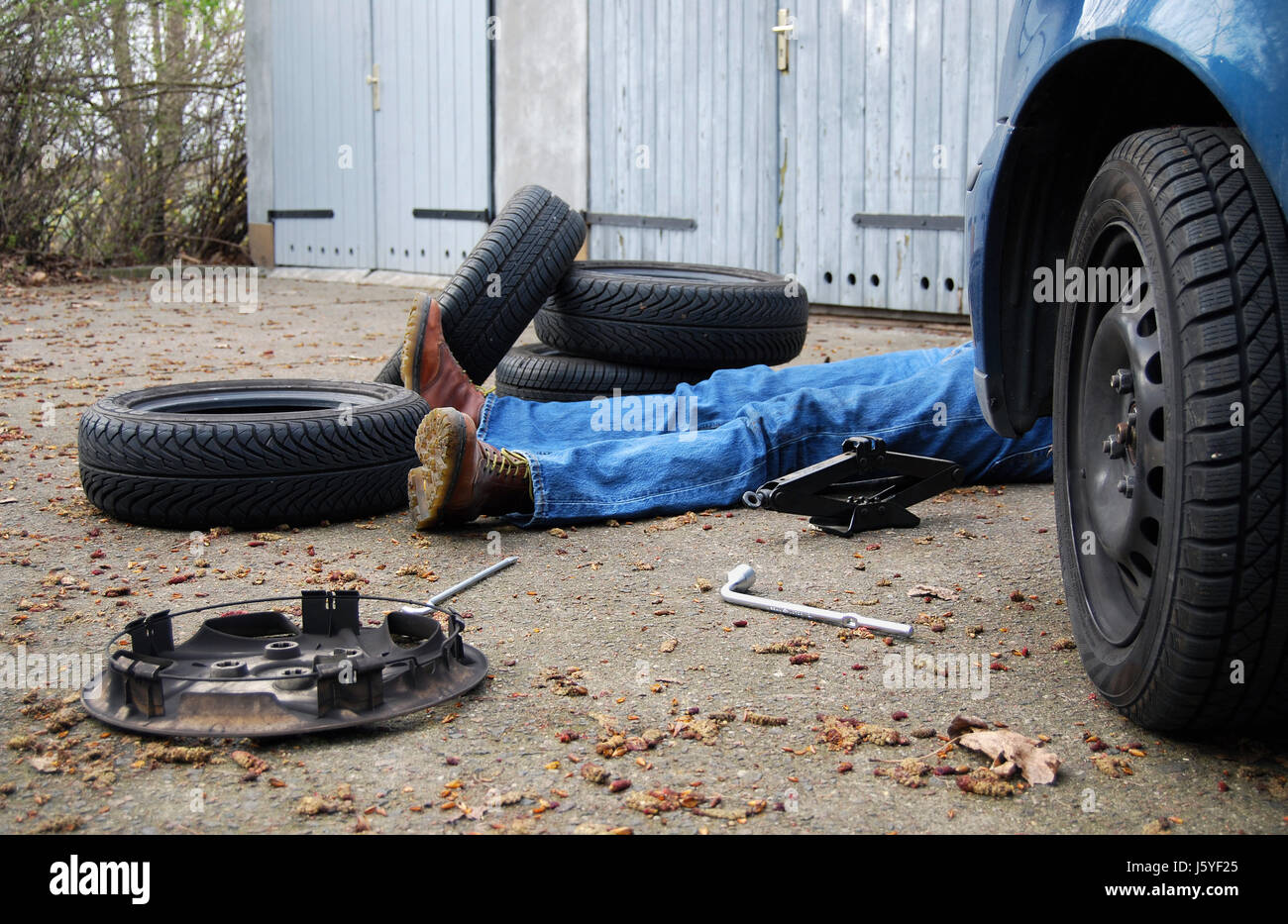 chaos layman change of tyres hub cap tyre tire tyres exhausted man make tool stock