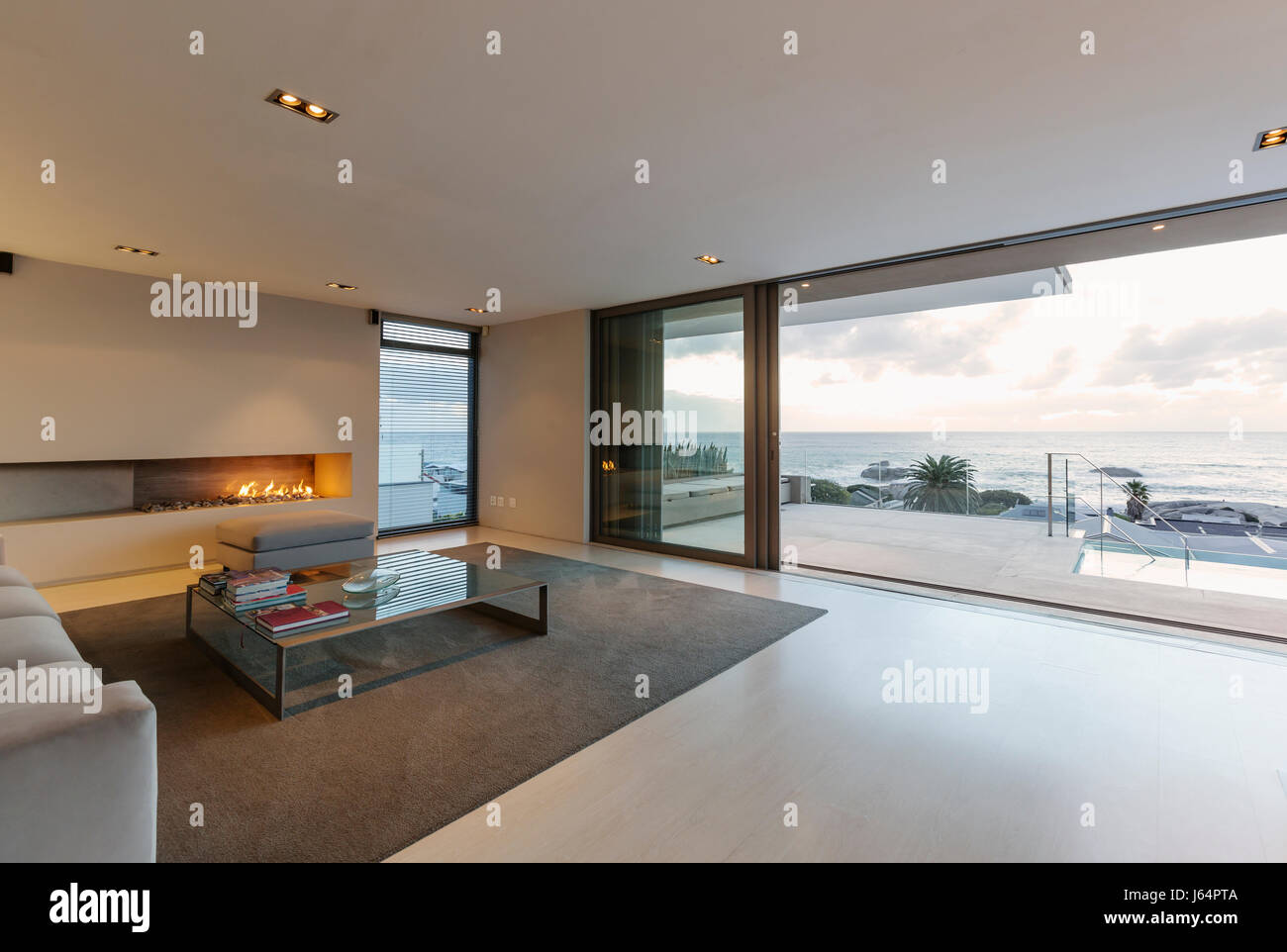 Modern Minimalist Luxury Living Room With Gas Fireplace And Patio Doors Open To Ocean View