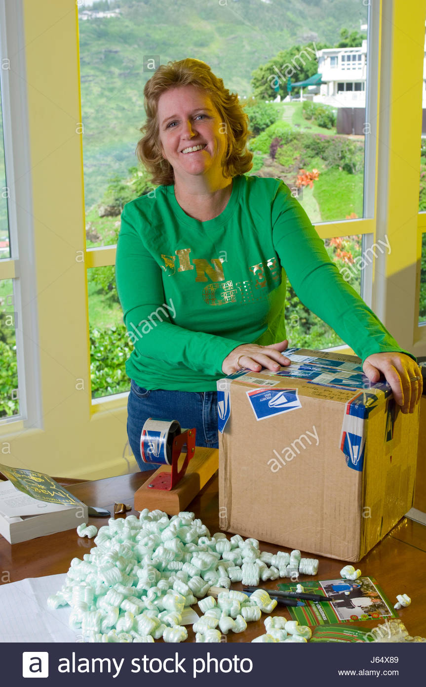Woman wrapping cardboard box full of Christmas gifts with USPS Stock ...
