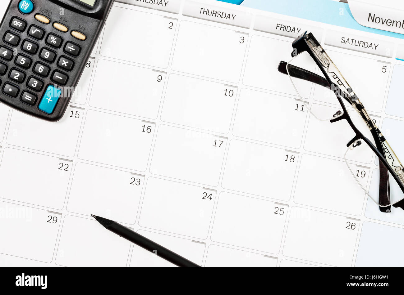 calendar schedule on work table and calculator pencil eye glasses