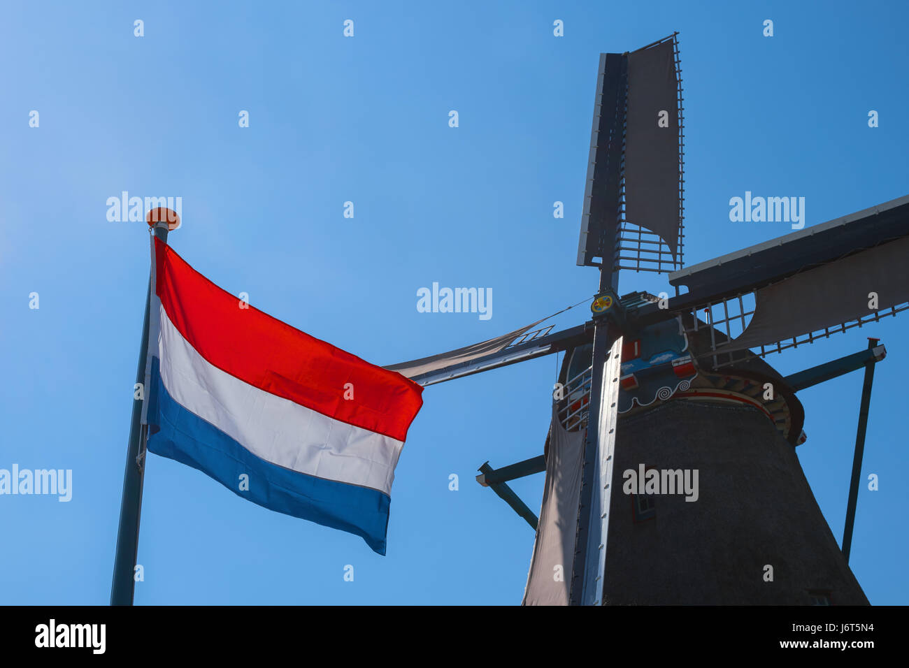 famous old dutch windmill and flag of the netherlands zaanse