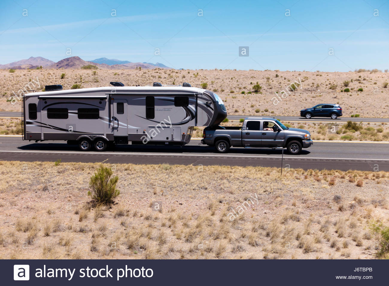 Pickup towing fifth wheel travel trailer on i 10 in southeastern arizona 3 people visible