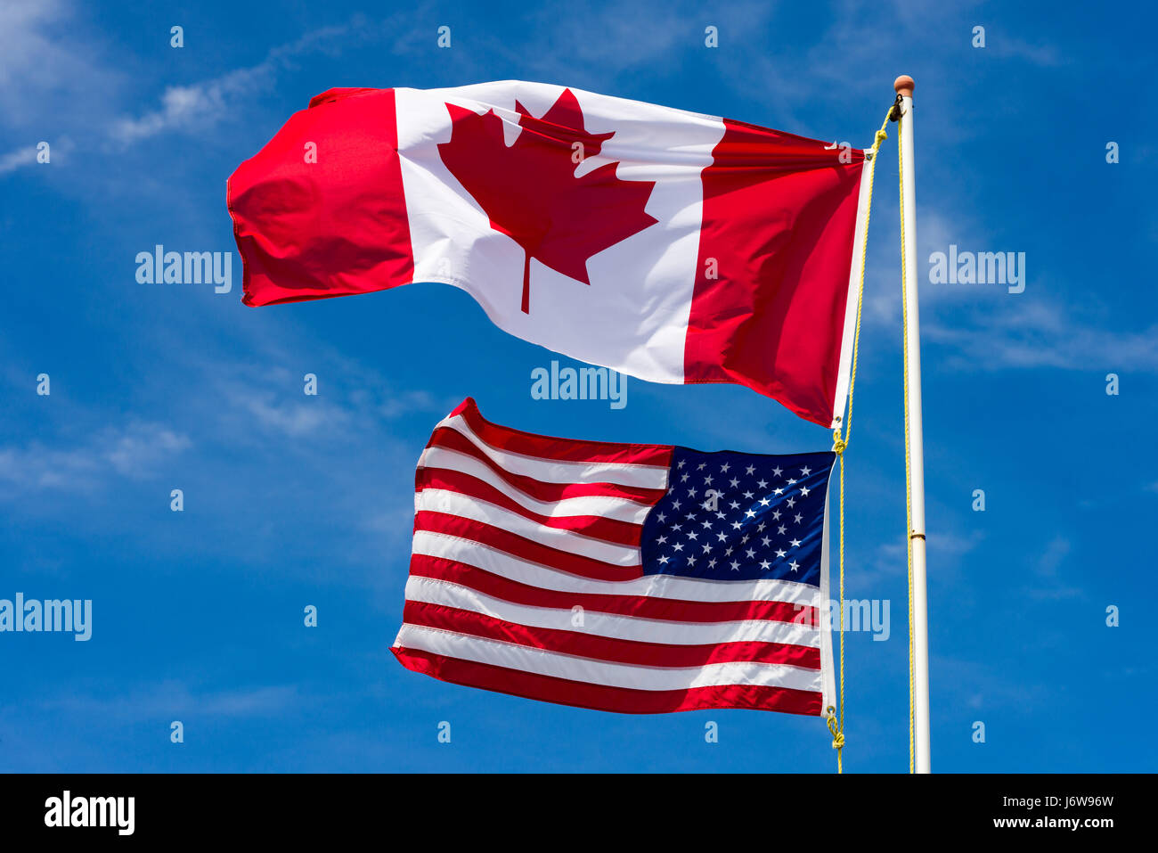 large canadian flag above smaller american flag in the wind stock