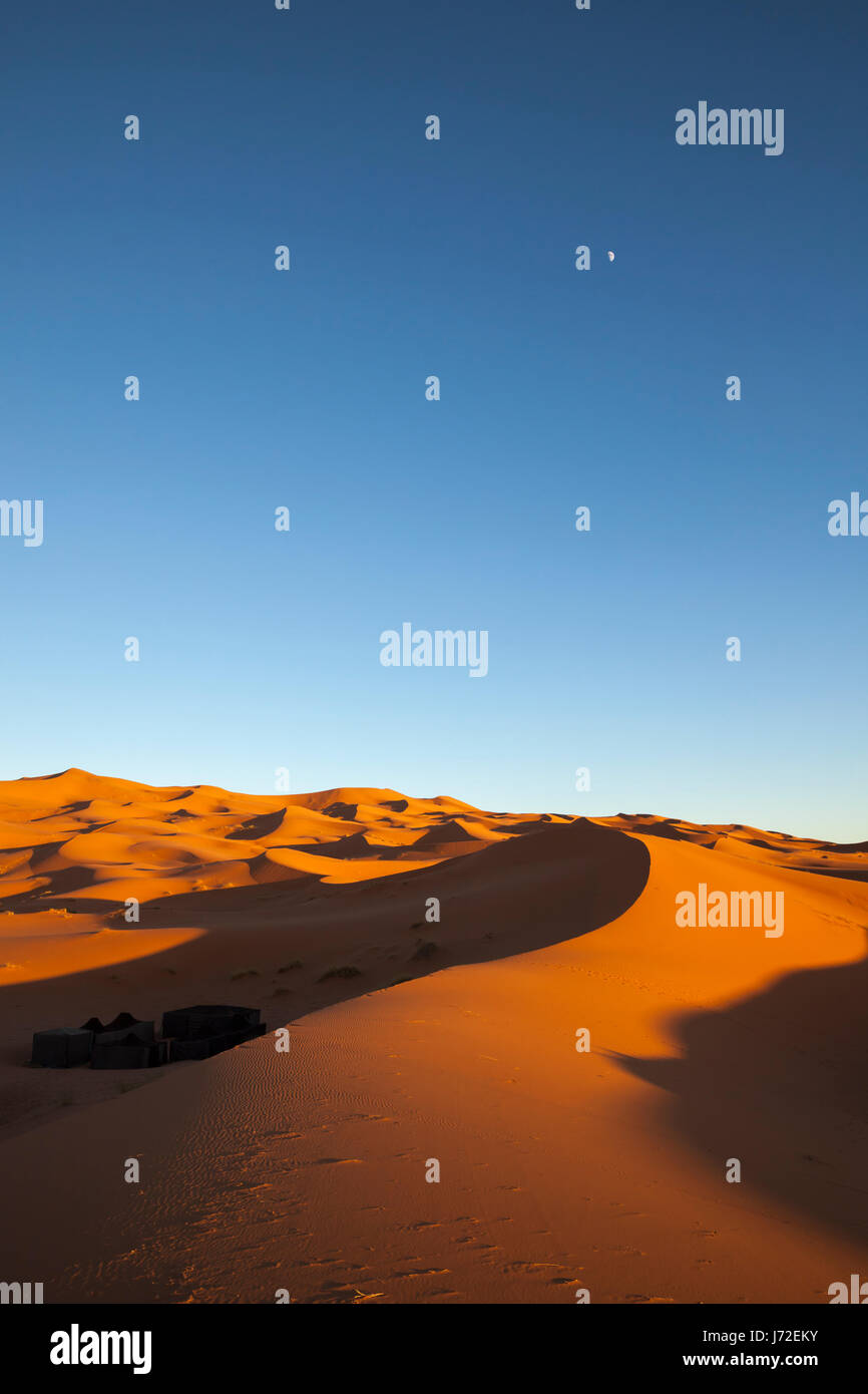 Tents in a dune shadow crescent moon on the clear sky at the desert near Merzouga Morocco & Tents in a dune shadow crescent moon on the clear sky at the ...