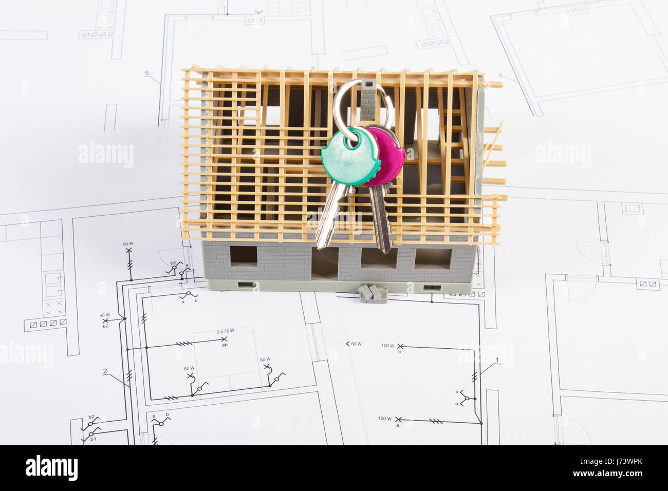 Small house under construction and home keys lying on electrical ...
