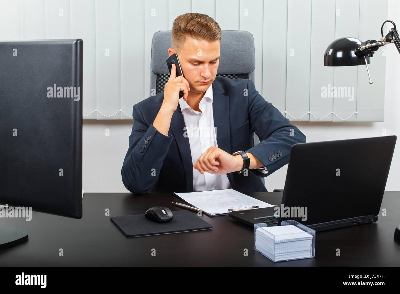 Frustrated office worker on the phone holding stock photo image - Frustrated Young Businessman Receiving An Unpleasant Phone Call Stock Image