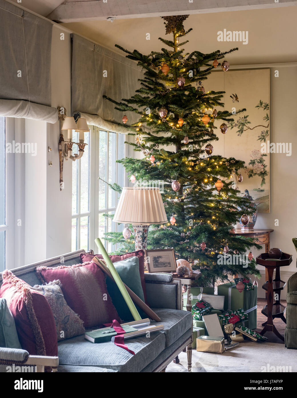 stock photo tall christmas tree in corner of spacious sitting room with settee and old chinese painted panels the sofa upholstery and blinds are from - Tall Christmas Tree