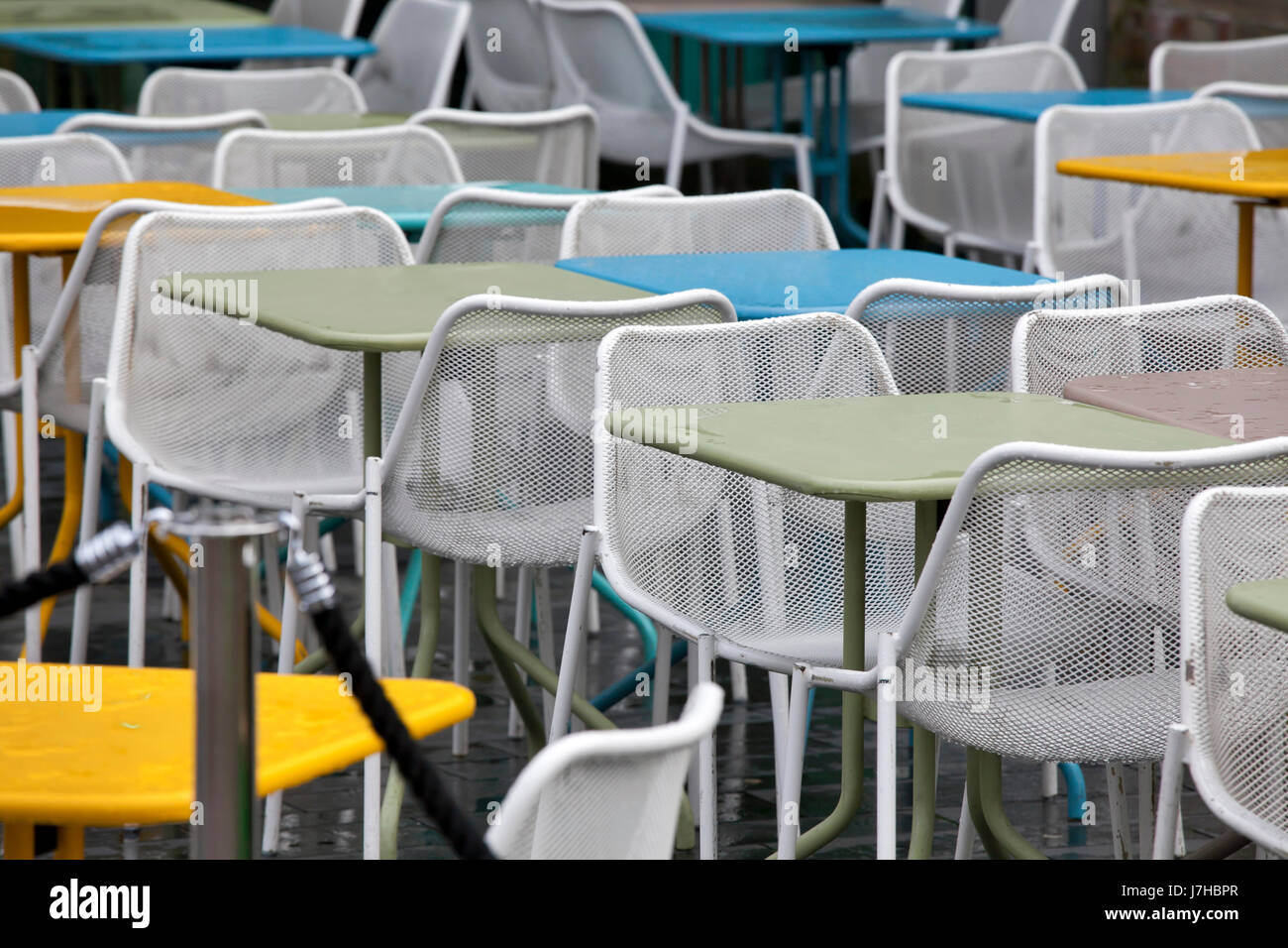 Restaurant Zone With Colorful Plastic Chairs And Blue, Yellow, White Tables  In The Lobby Of The Mall. Beautiful Interior