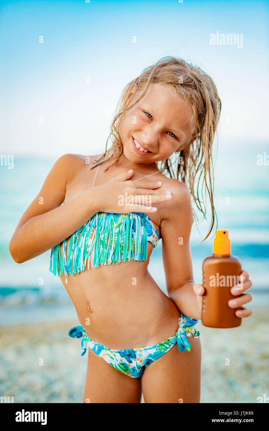 Cute Little Girl Applying Suntan Lotion On The Beach And