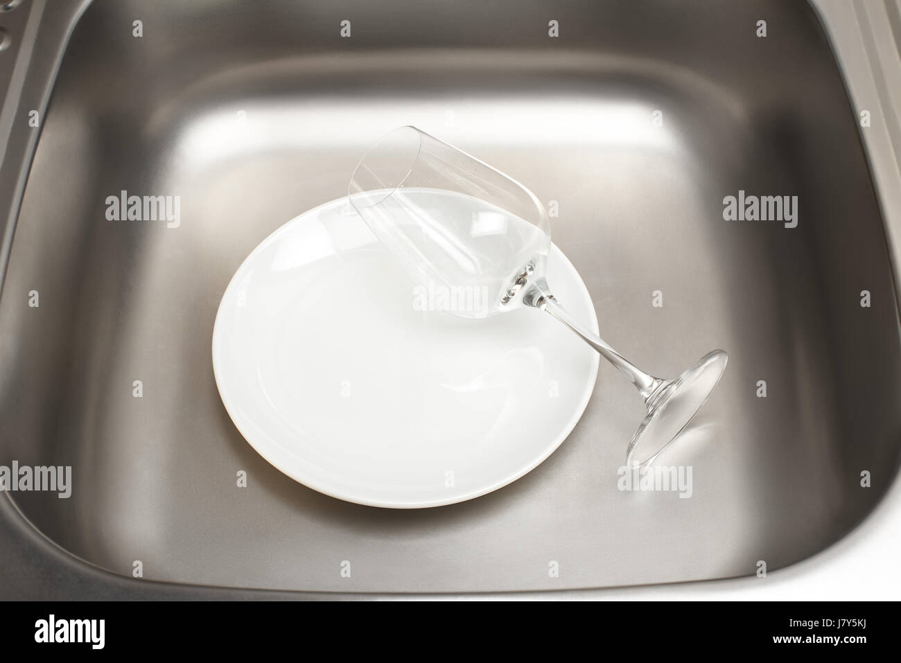 Close up kitchen sink with clean white plate and wine glass Stock ...