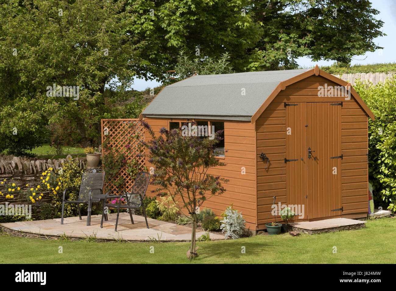 a dutch barn style garden shed with a patio in a english country garden - Garden Sheds With Patio