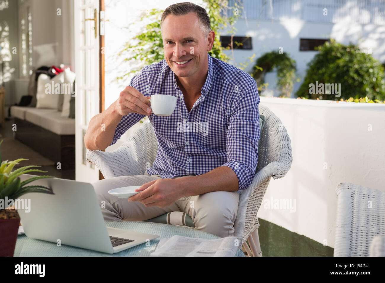 portrait of mature businessman drinking coffee while sitting