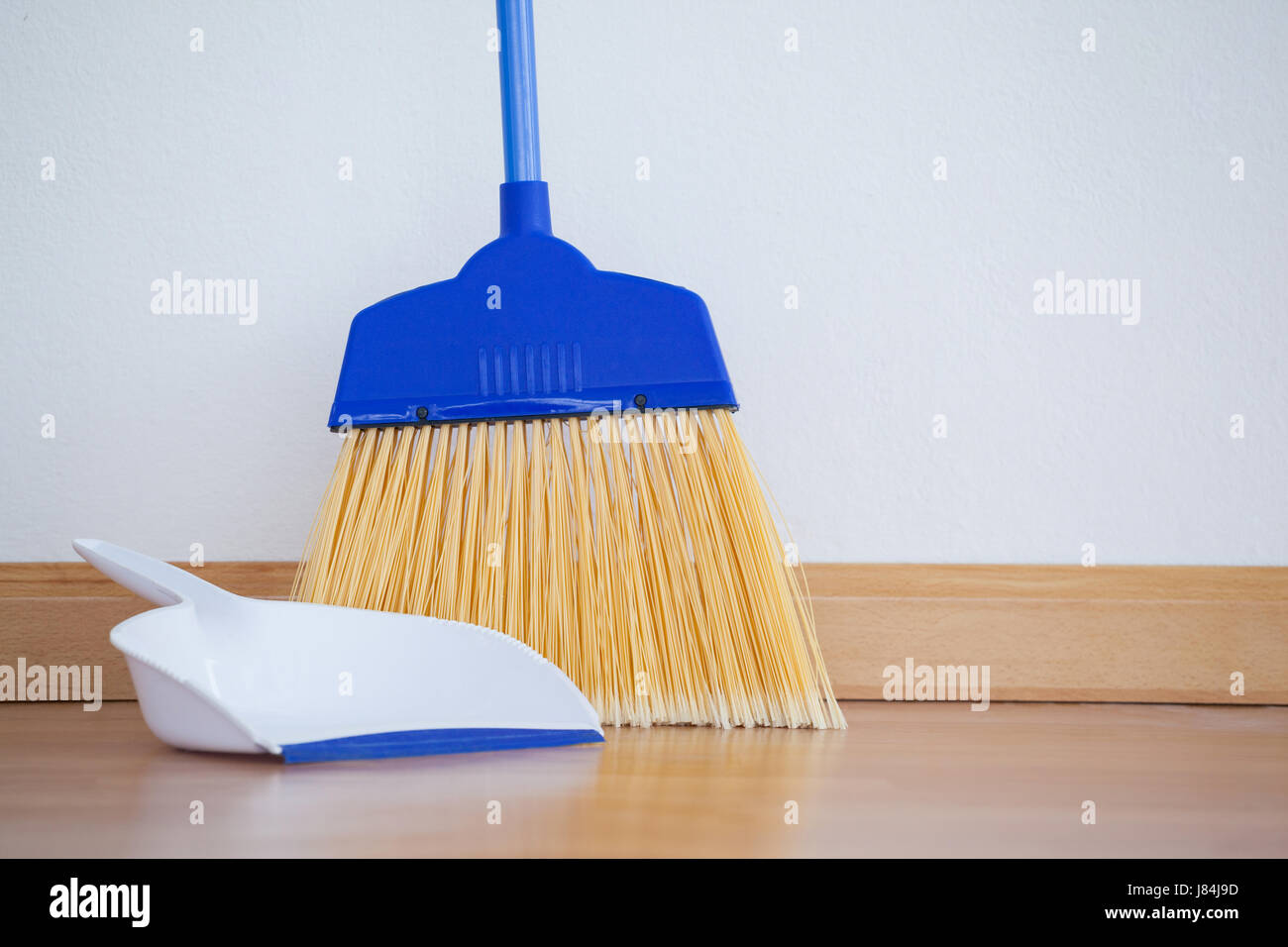 close-up of dustpan and sweeping broom on wooden floor stock photo