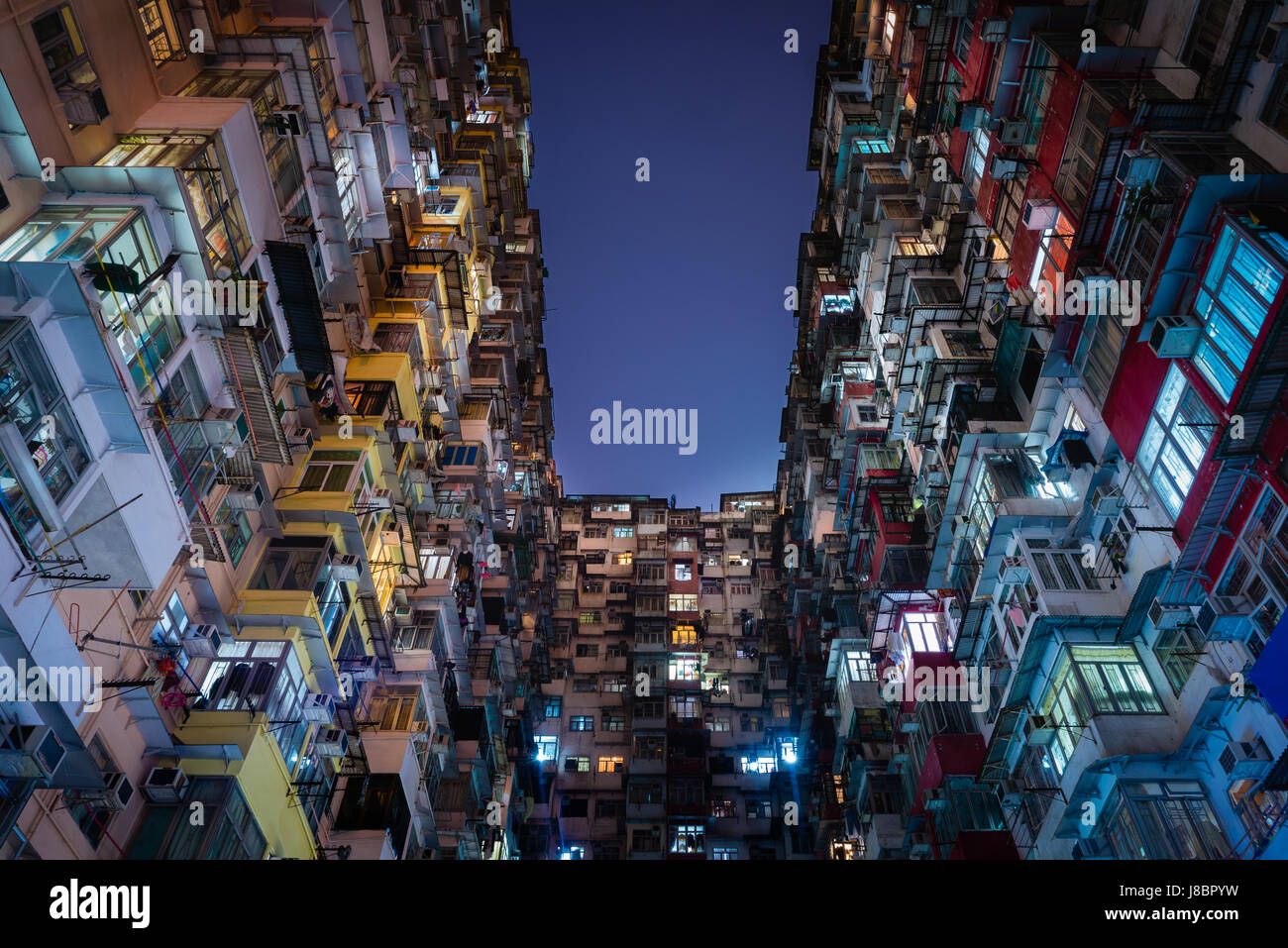 Apartment Building At Night exterior of old hong kong apartment building at night stock photo