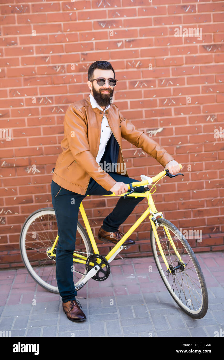 Cool Young Bearded Hipster Besides A Fixie Bicycle On The Street