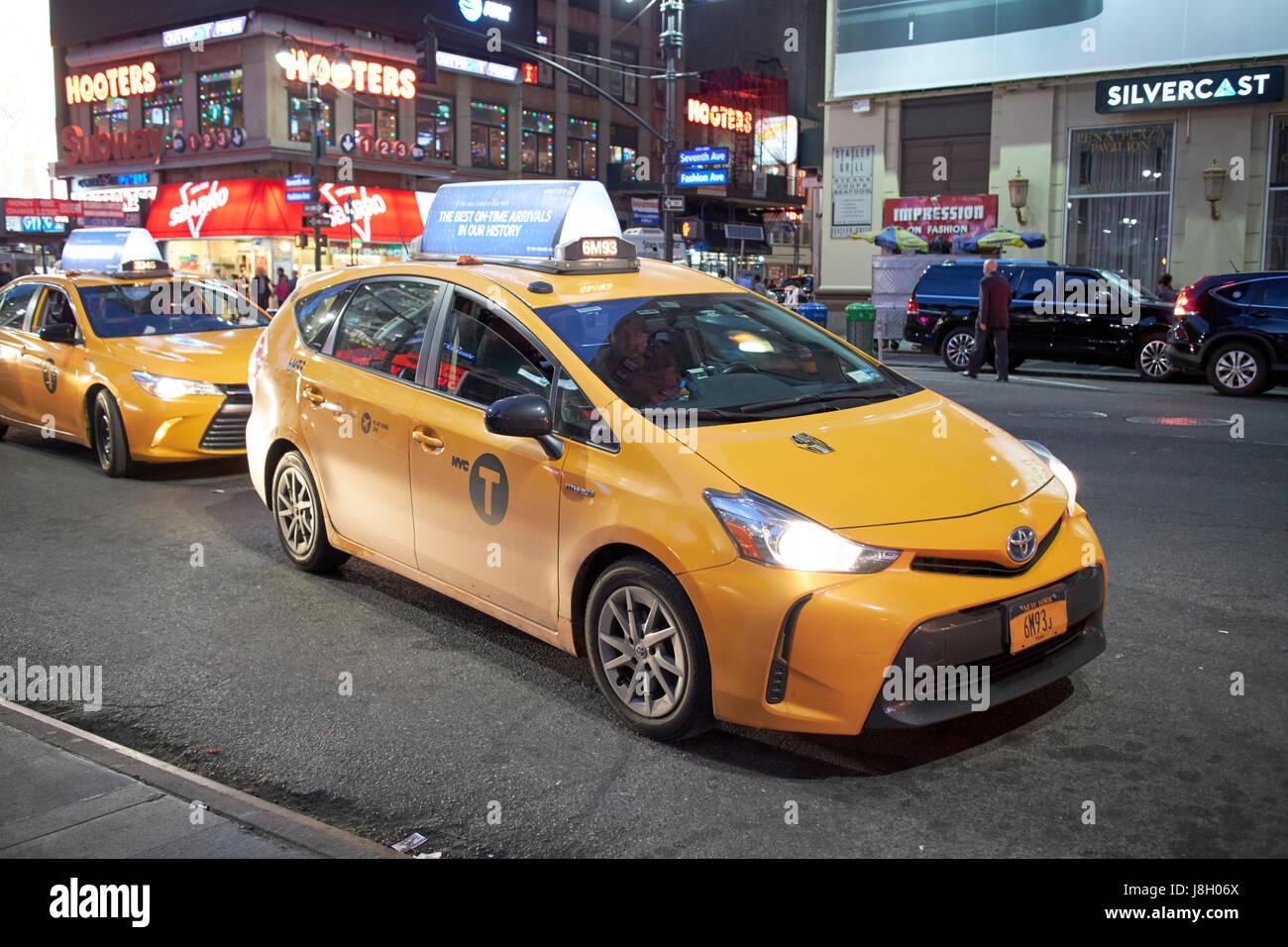 Toyota prius v hybrid new york city yellow cab at night in midtown usa stock