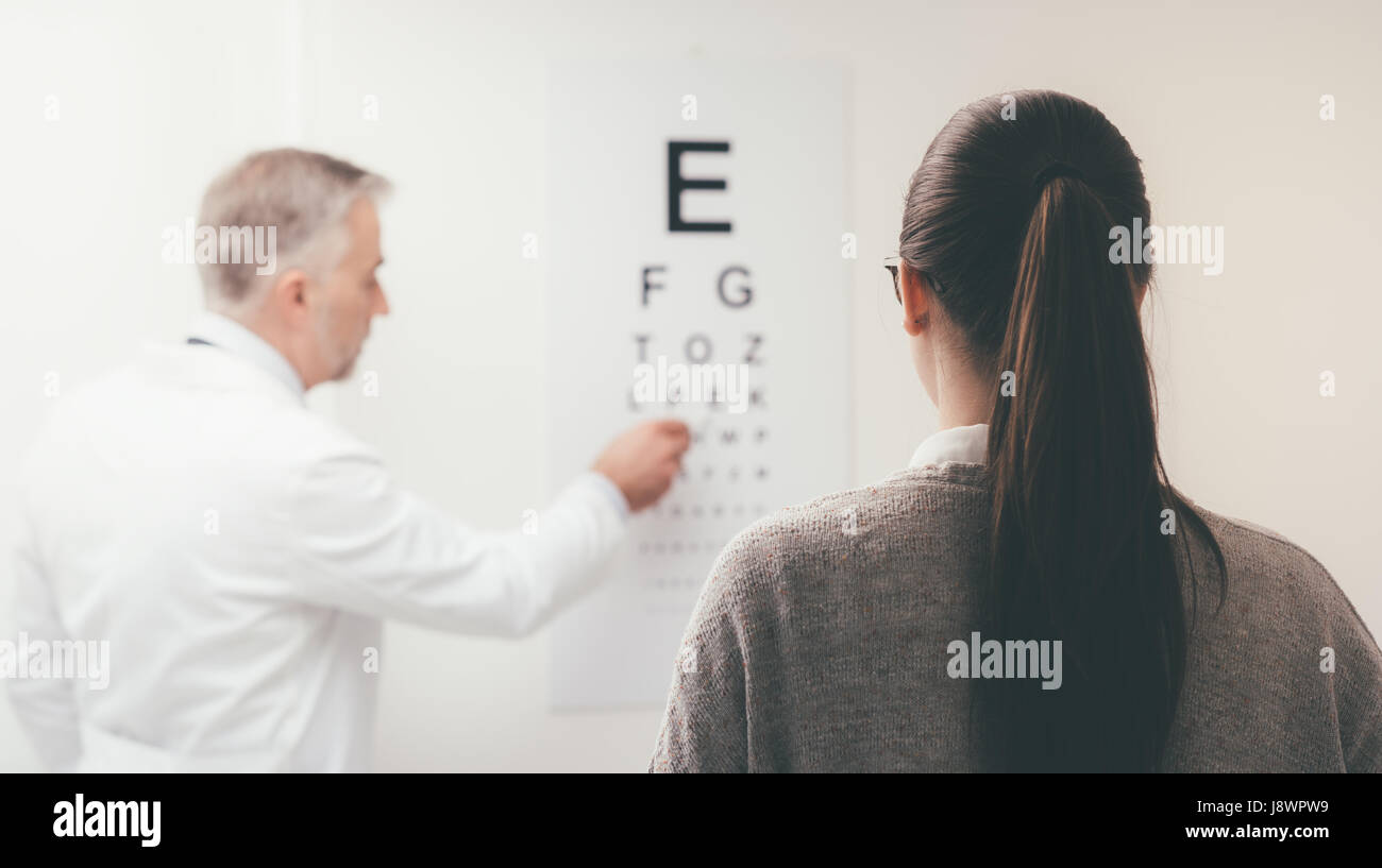 Woman reading the eye chart the ophthalmologist is pointing at woman reading the eye chart the ophthalmologist is pointing at one letter and examing the patient eye care concept nvjuhfo Image collections