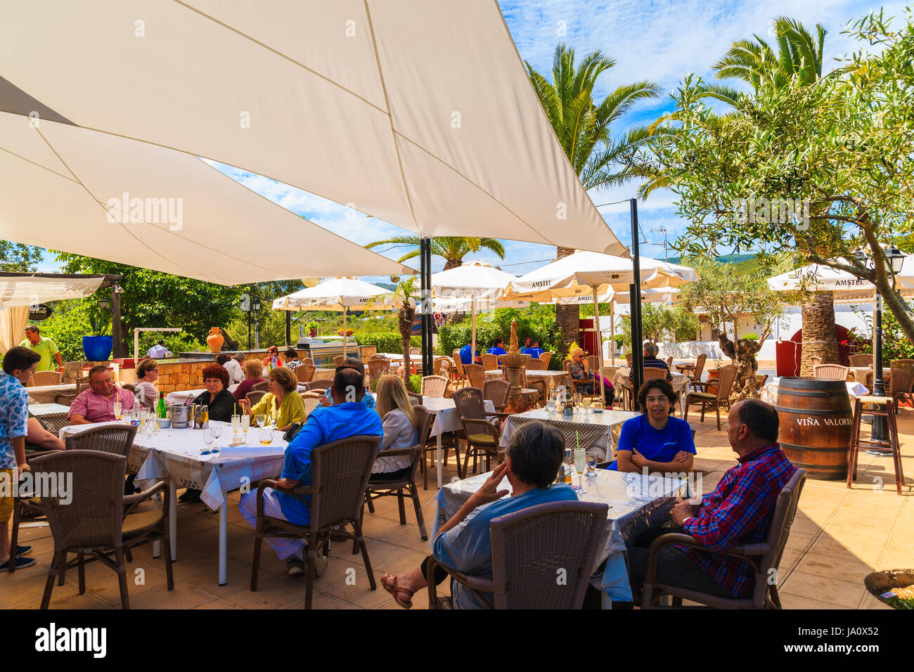 ibiza island, spain - may 18, 2017: people dining in garden of