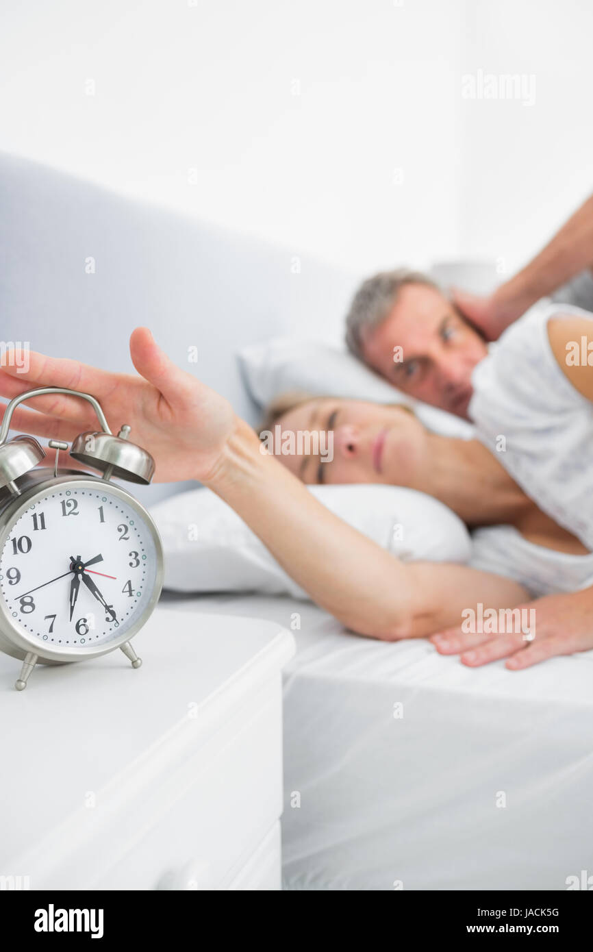Stock Photo   Tired Wife Turning Off Alarm Clock As Husband Is Covering  Ears In Bedroom At Home