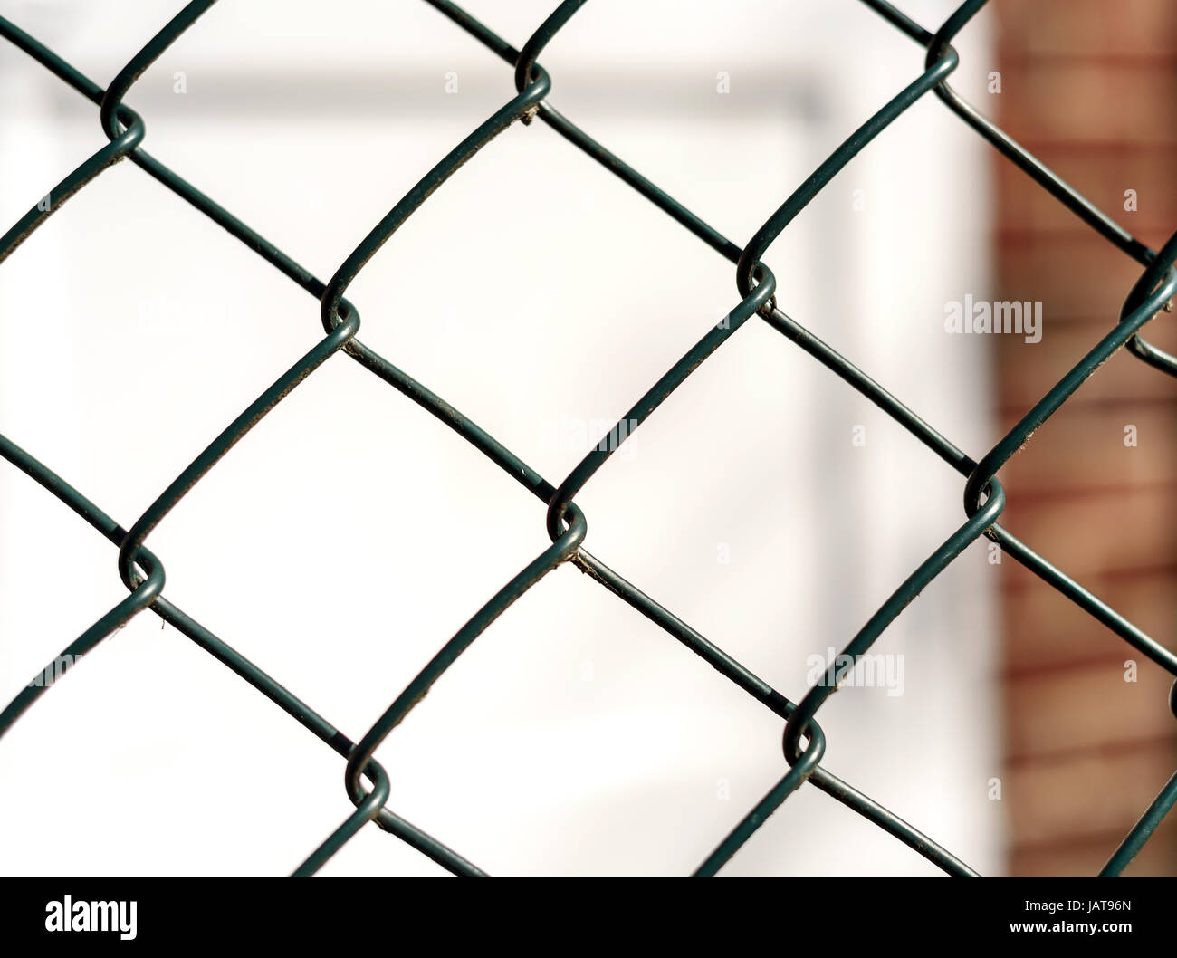Single Chain mesh link fence with a defocused white door in the ...