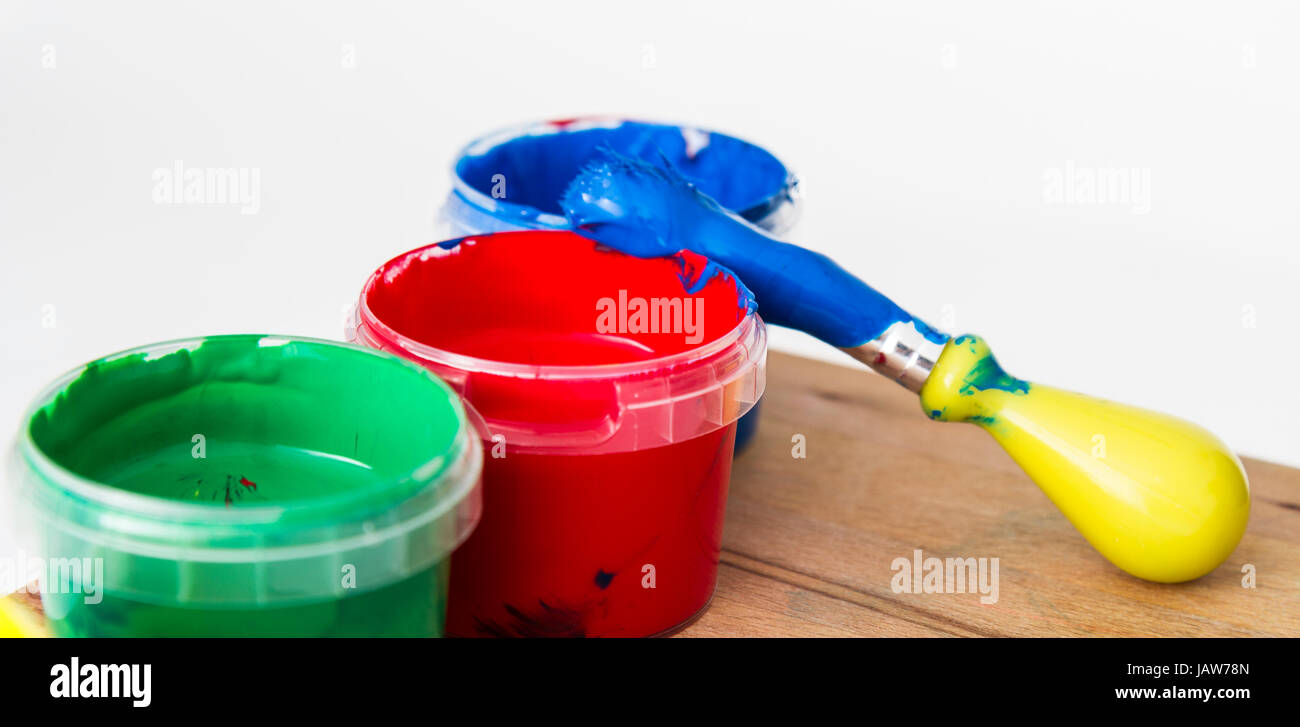 paint in small tubs with paint brush on wooden table Stock Photo ...