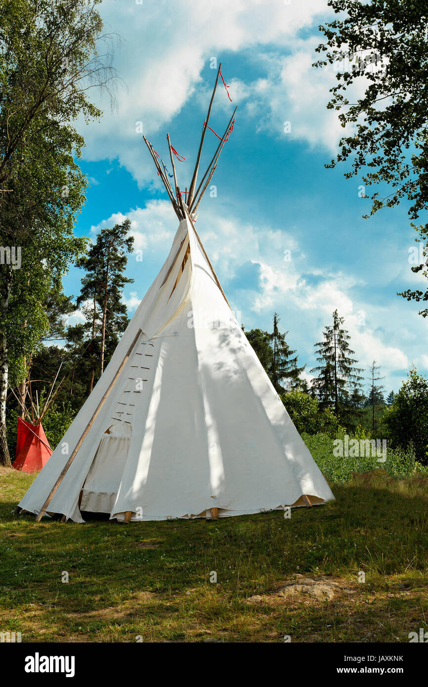 A tipi (also tepee and teepee) is a conical tent traditionally made of animal skins and wooden poles against blue sky & A tipi (also tepee and teepee) is a conical tent traditionally ...