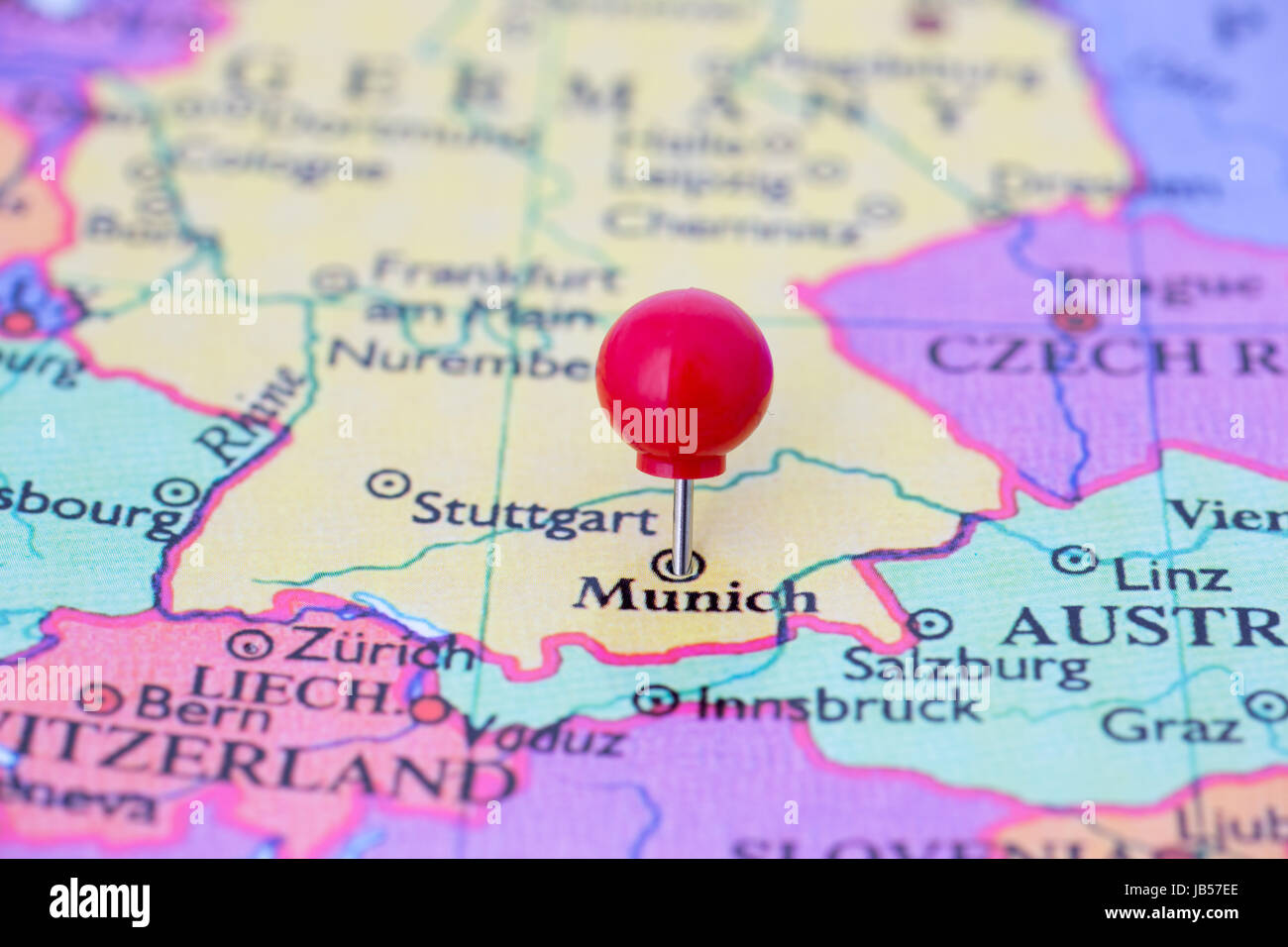 Round red thumb tack pinched through city of Munich on Germany map