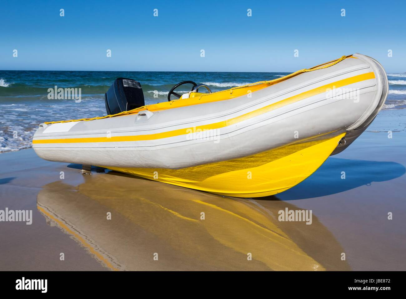 Stock Photo   Yellow And White Rubber Duck Inflatable Boat On The Sandy  Beach