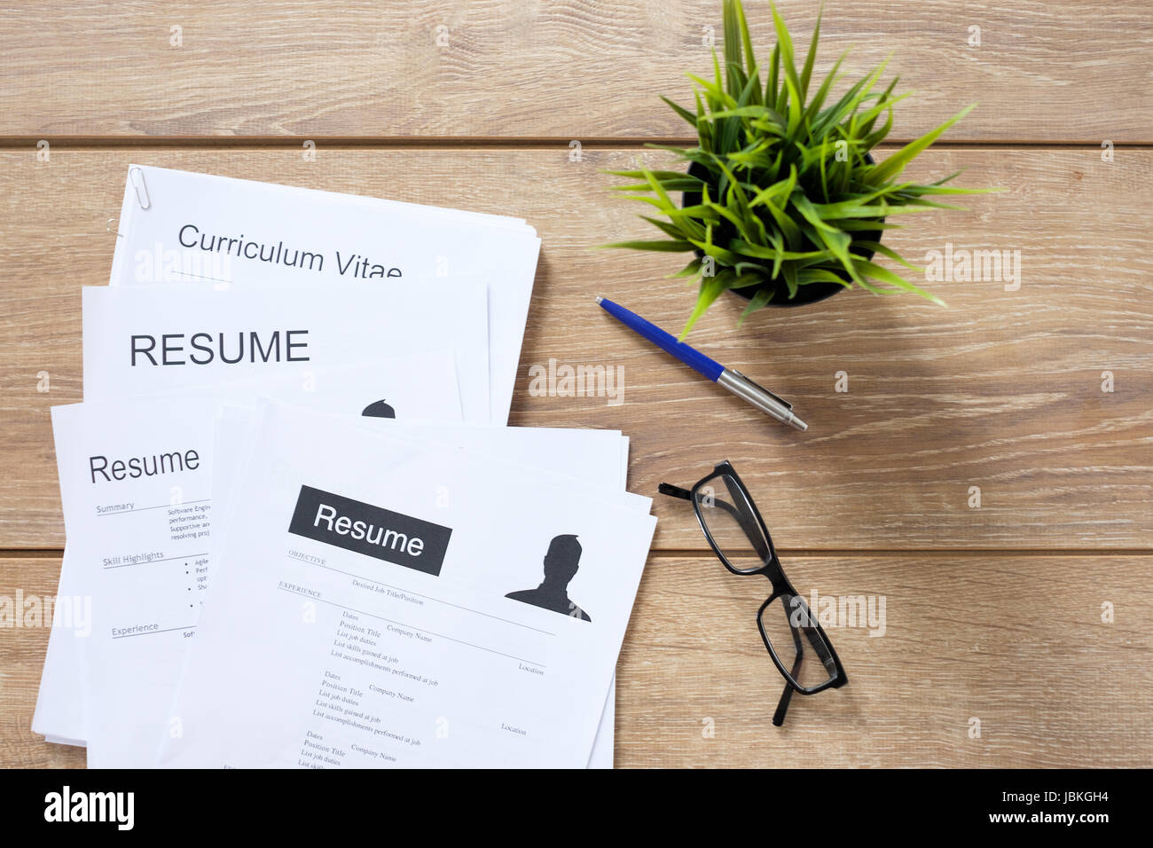 Resume Applications On Wooden Desk Ready To Be Reviewed Stock