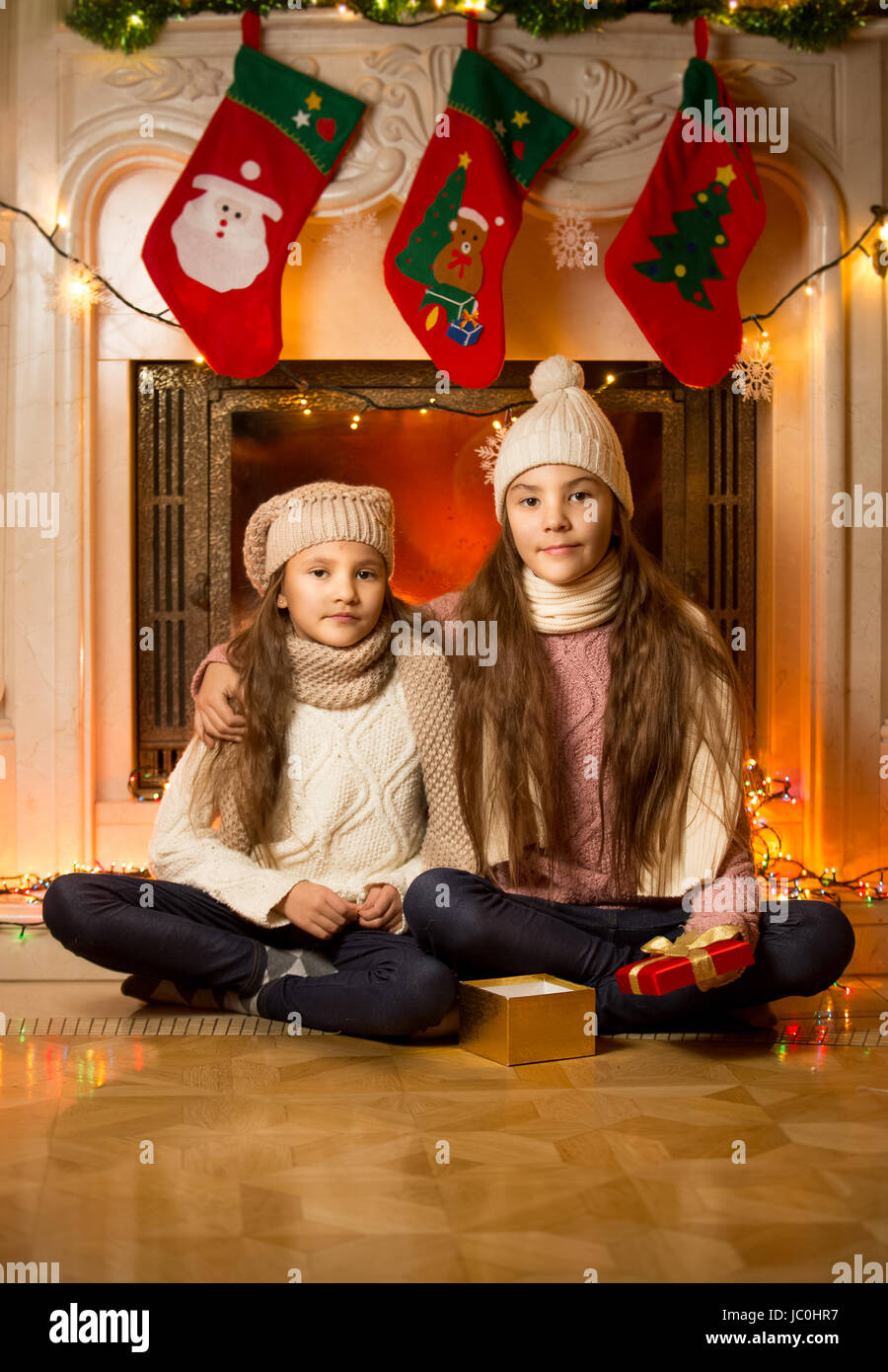 portrait of two cute girls sitting next to decorated fireplace for