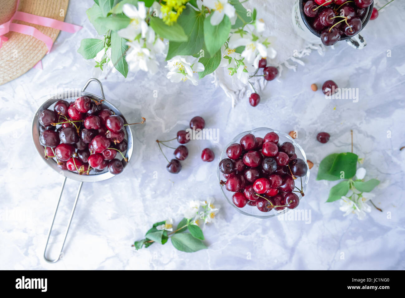 Top view fresh cherry fruit in glass vase other dishes with top view fresh cherry fruit in glass vase other dishes with berries and jar with jasmine and wildflowers on the light marble table soft selective fo reviewsmspy