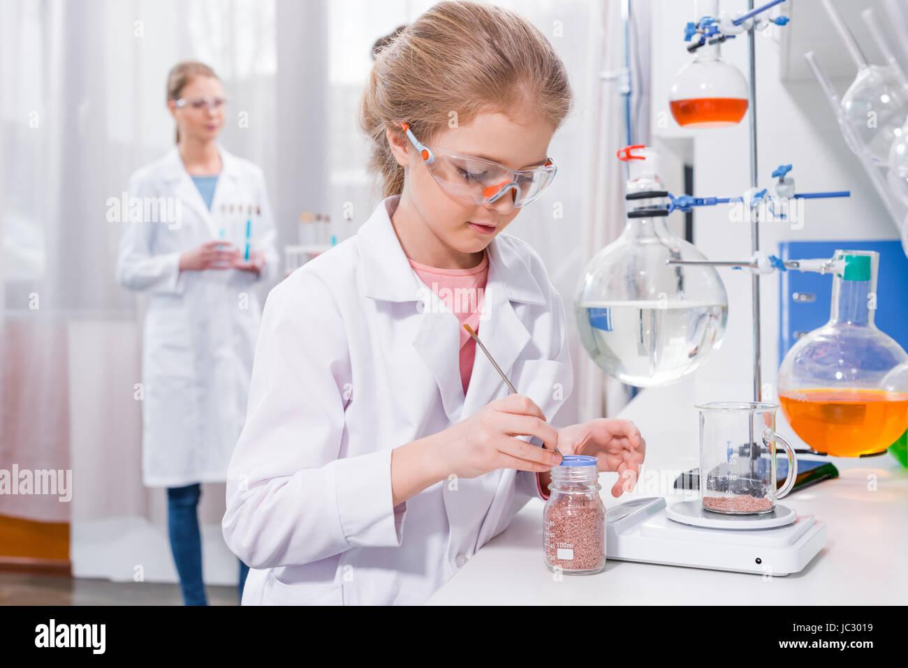Little girl scientist in white coat making experiment in chemical ...