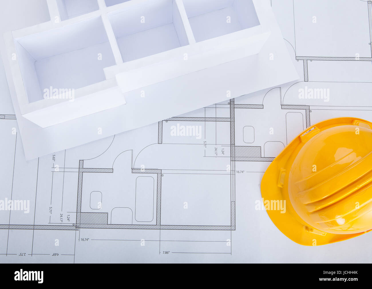 High angle view of house model on blueprint with hardhat stock photo high angle view of house model on blueprint with hardhat malvernweather Choice Image