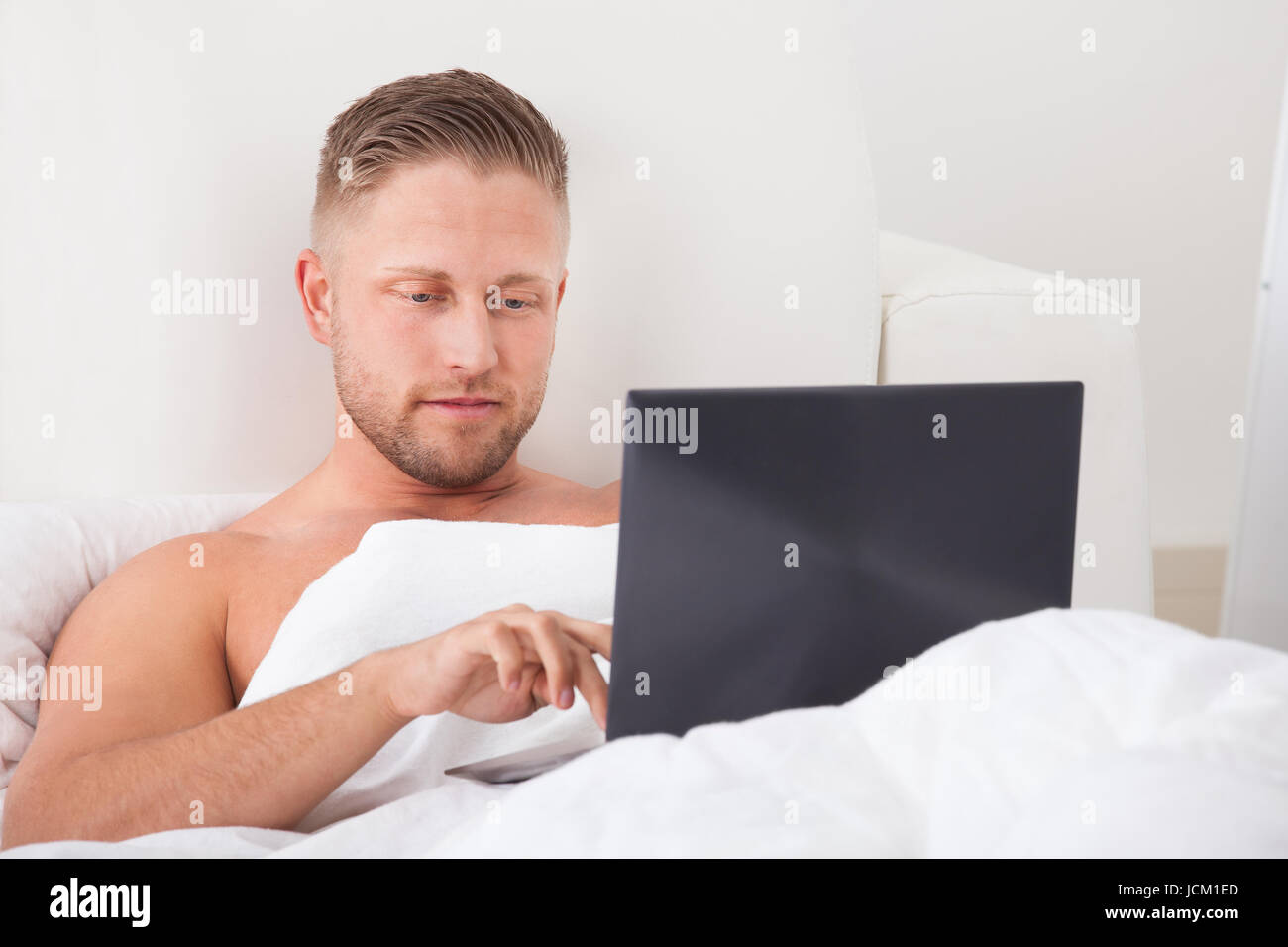 Man Sitting Up In Bed Against The Pillows Working On A Laptopputer  Smiling As He Reads The Screen