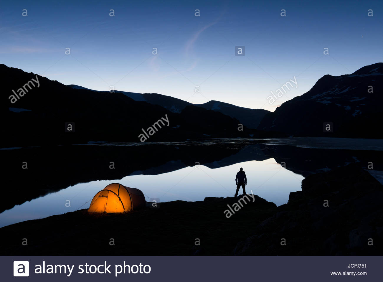 Tenting at the Øvre Pikhaugvatnet lake a calm summer night. Glomdalen valley in the Saltfjellet-Svartisen National Park in Norway & Tenting at the Øvre Pikhaugvatnet lake a calm summer night ...