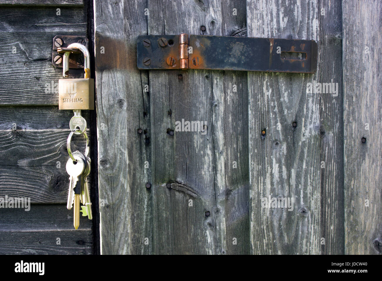 Black hasp and staple or clasp with padlock and keys. The garden shed door is unlocked and the keys are still in the lock. The staple clasp is open & Black hasp and staple or clasp with padlock and keys. The garden ...