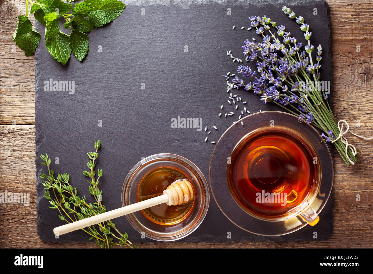 Herbal tea in a glass cup honey different types of herbs Stock