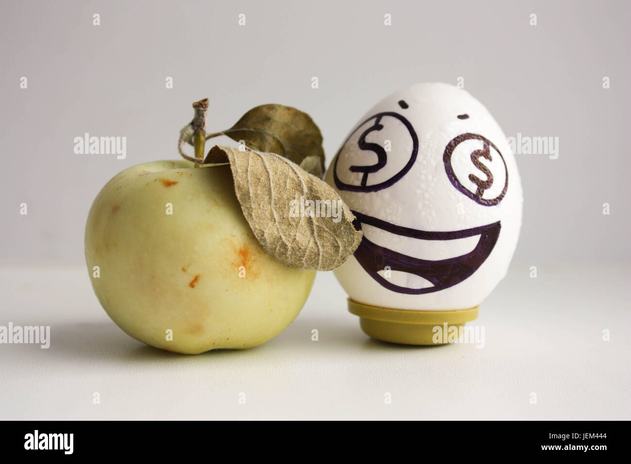 Business Concept An Egg With Eyes Dollars And An Apple A Good Business Idea Money Apple Photo For Your Design