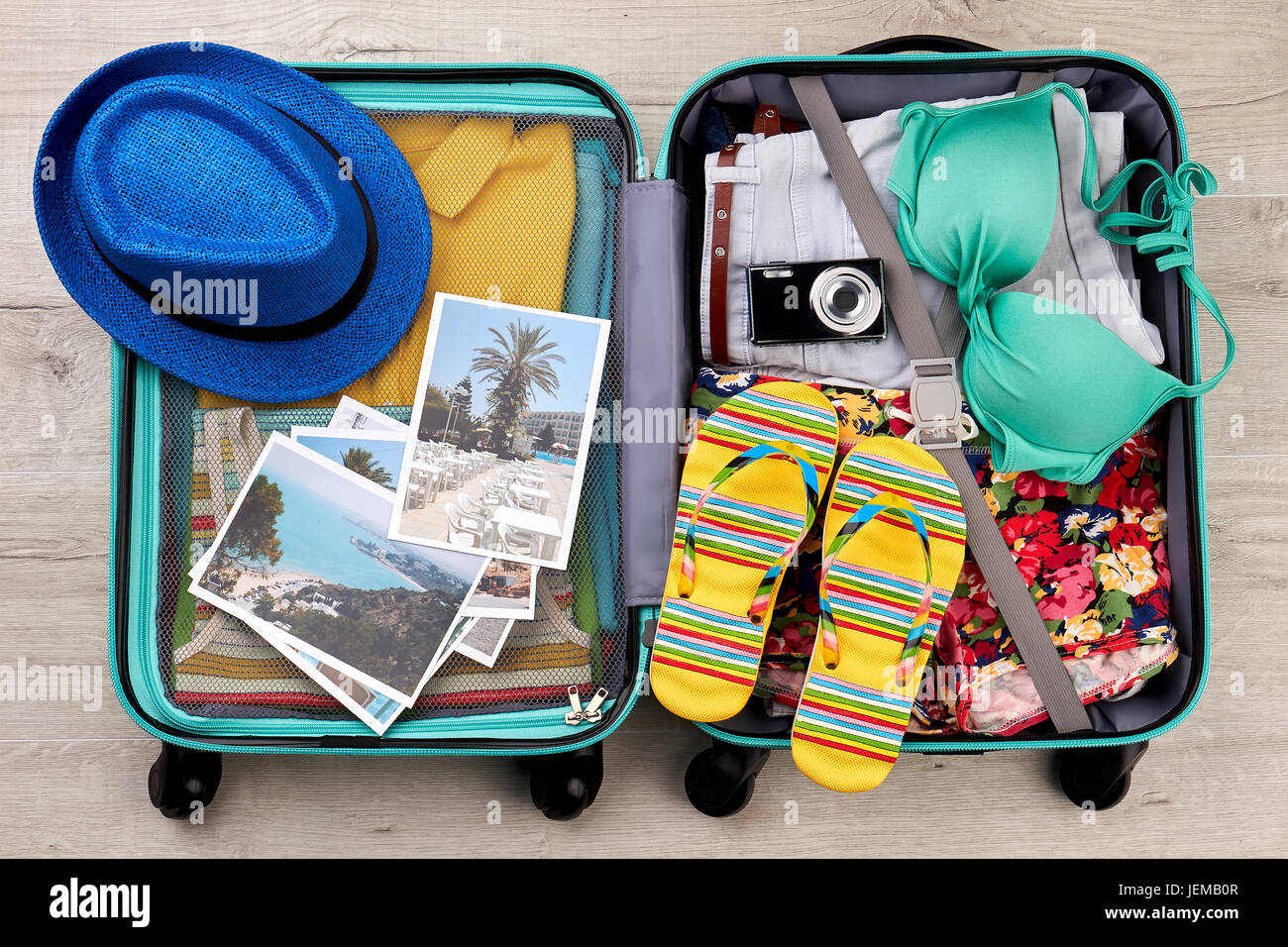 Suitcase full of beach accessories. Opened bag with summer ...