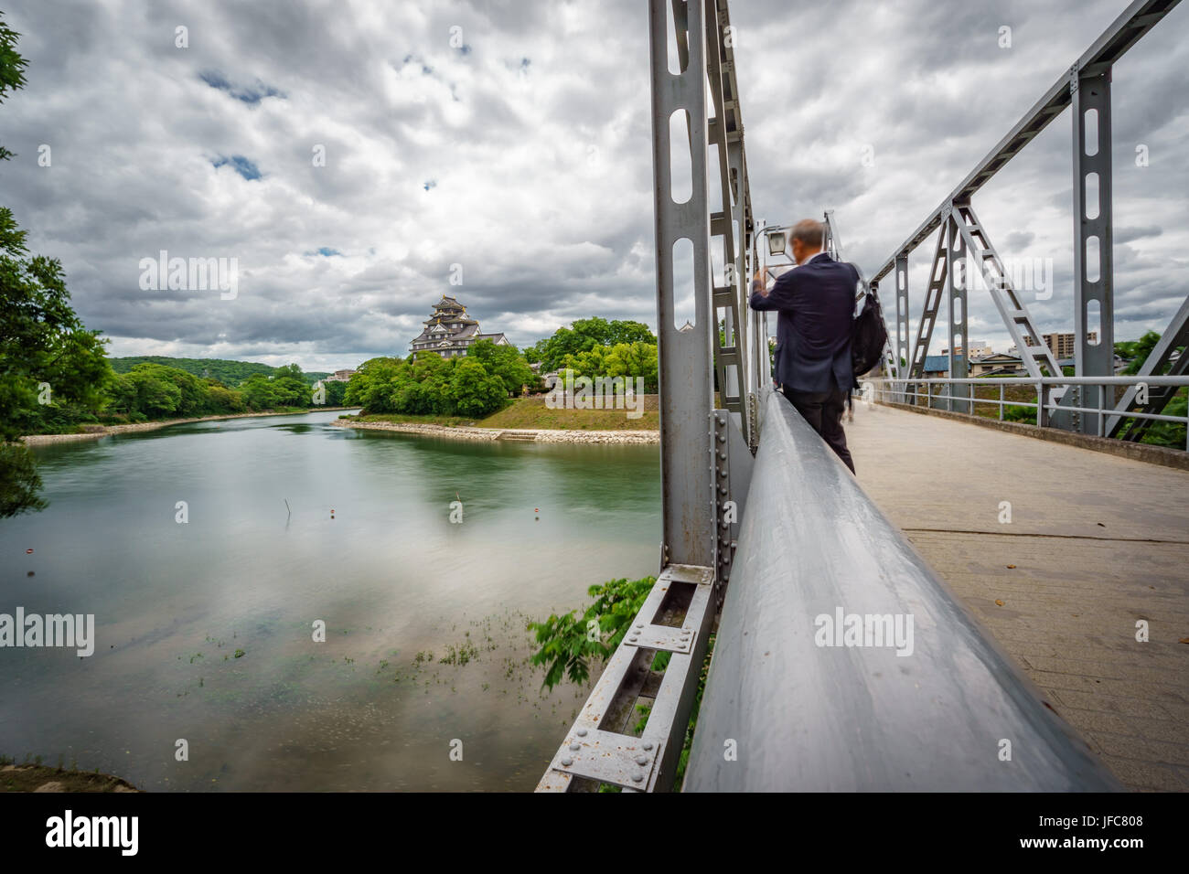 Wide angle view of iron bridge with tourist taking photo to Okayama Castle  or Crow Castle