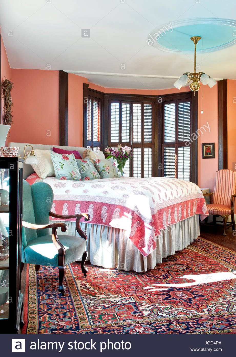 Bedroom With Salmon Colored Walls, Aqua Wing Back Chair, Oriental Rug,  Quilt, Period Chandelier, Interior Shutters, Bed Quilt, Flowers