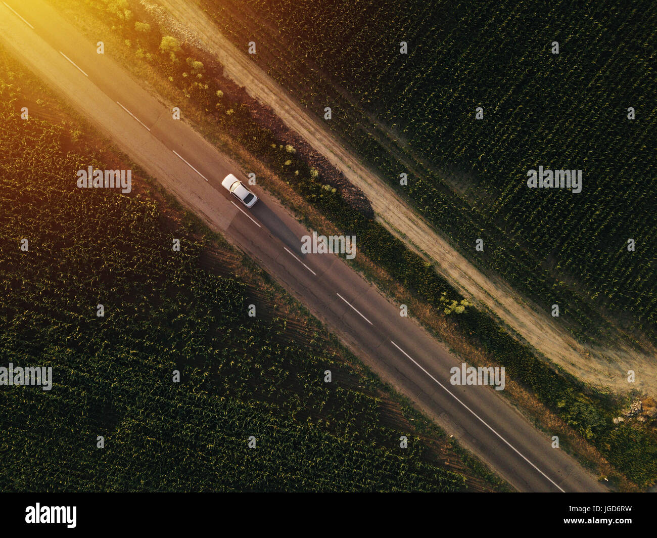 Aerial View Of Lonely Car On The Road Driving Towards Sunset Drone Point