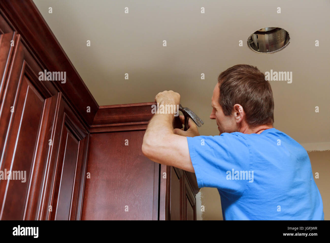 Carpenter Brad Using Nail Gun To Crown Moulding On Kitchen Cabinets Framing  Trim, With The