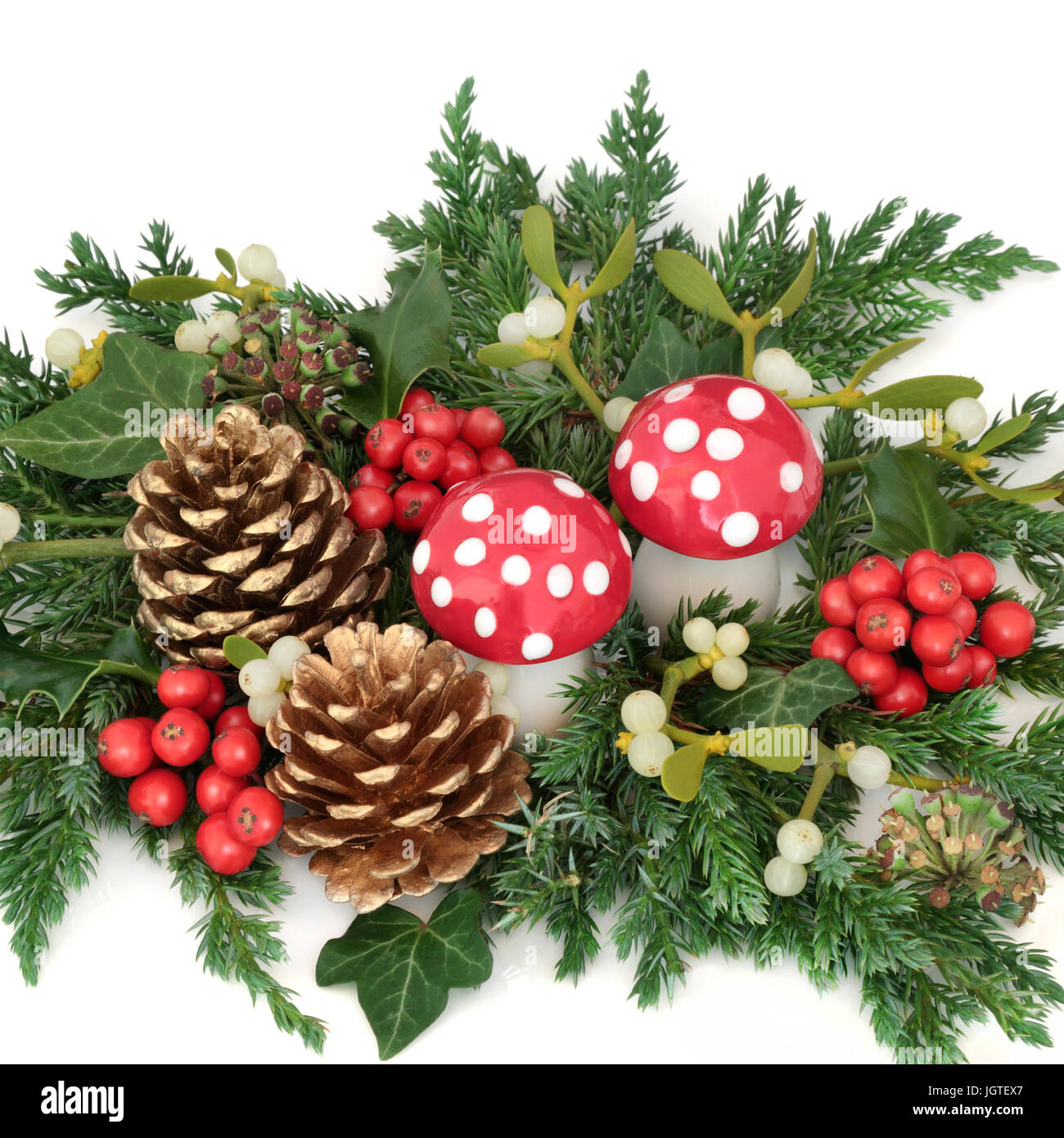 christmas decoration with holly fly agaric mushroom ornaments gold pine cones mistletoe and
