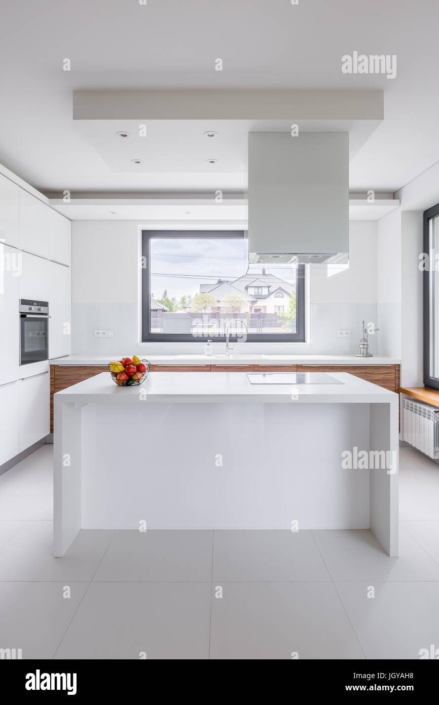 Stylish, white kitchen with island, exhaust hood and window Stock ...