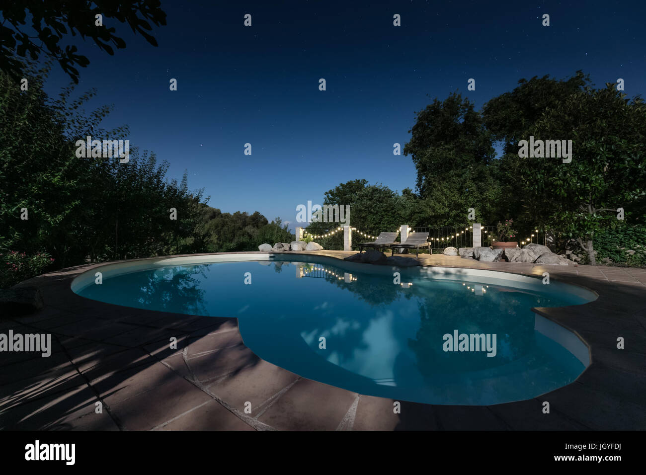 Moonlight lighting up a swimming pool on a clear deep blue starry night with two sunbeds and trailing lights reflecing in the still water & Moonlight lighting up a swimming pool on a clear deep blue starry ... azcodes.com