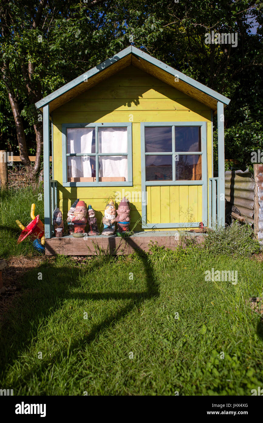 a small painted wood house for children to play in with gnome