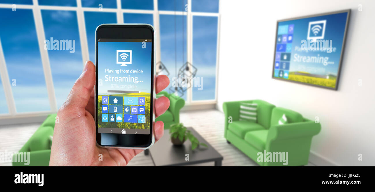 Cropped Hand Holding Smart Phone Against Green Sofas In Living Room At  Modern House
