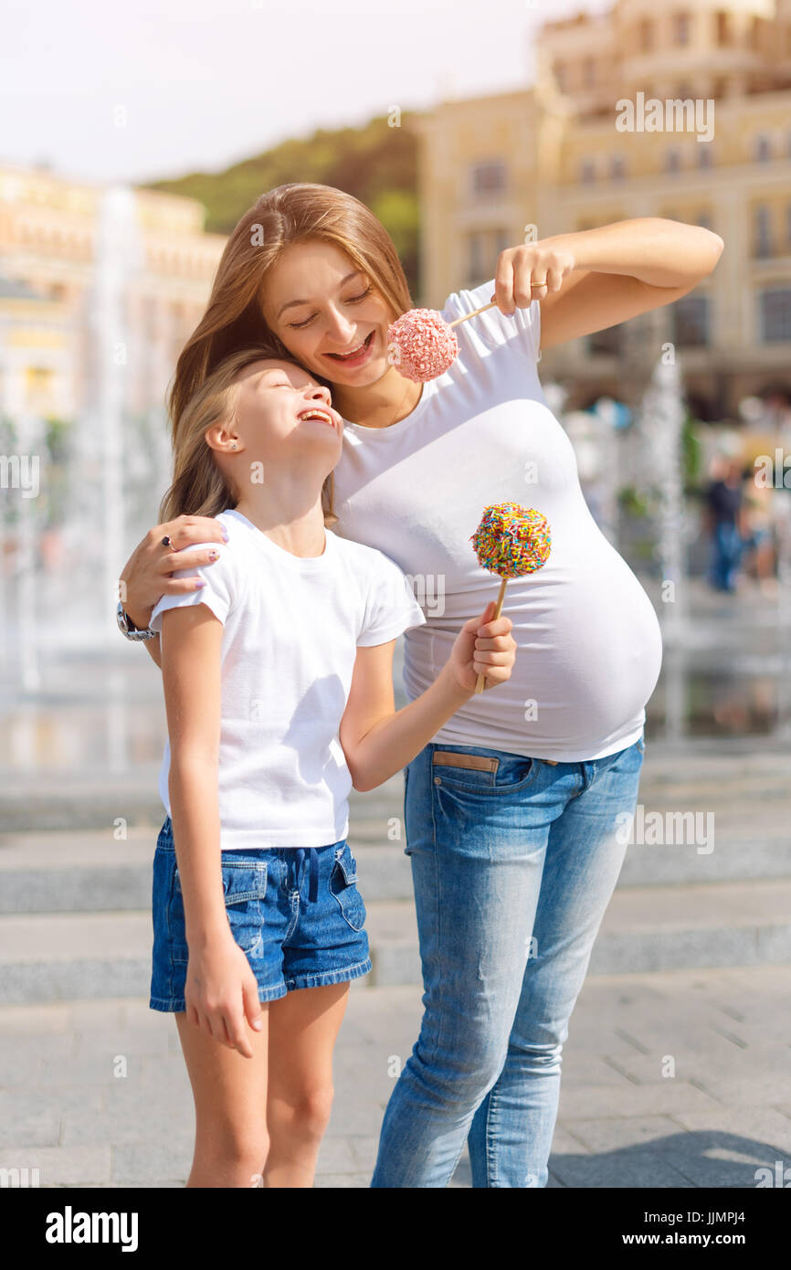 Images Of Candy Loving Beautiful cute little girl and her pregnant mother eating candy apples at