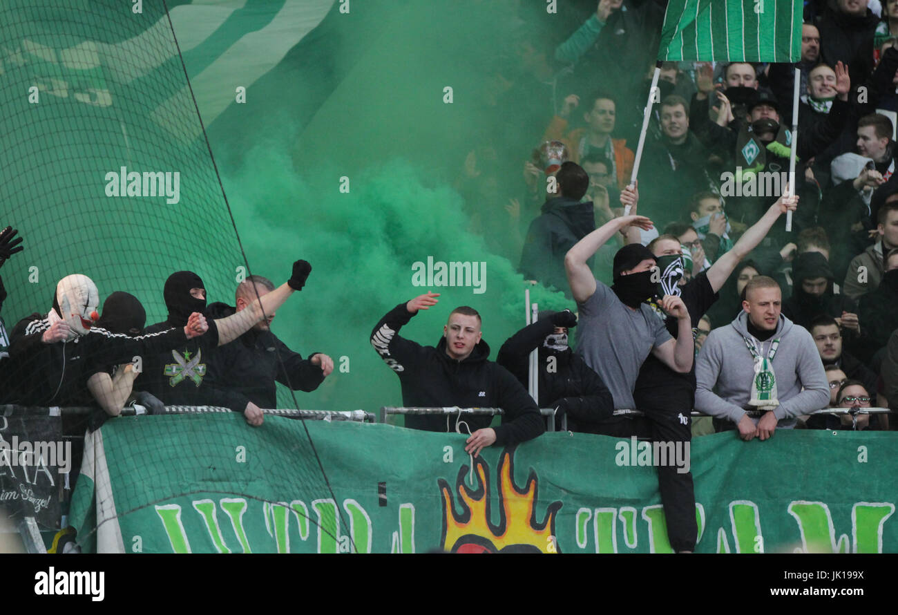 hooded ultras of werder bremen ignite green smoke bombs and flairs